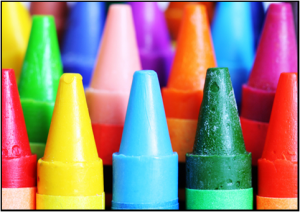 Close-up of a box of Crayons.  Seeing mostly the tops and different colors of the Crayons.