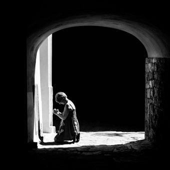 women kneeling and praying, seen through a stone doorway