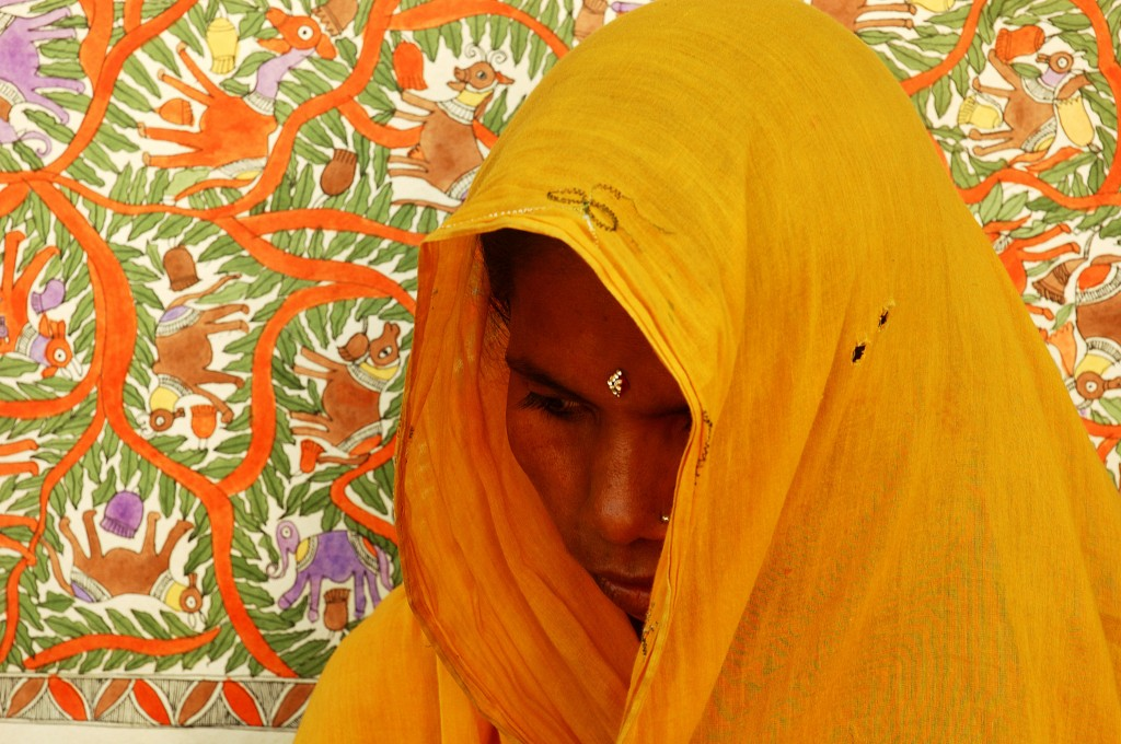 Indian worman looking down, wrapped in a golden shawl